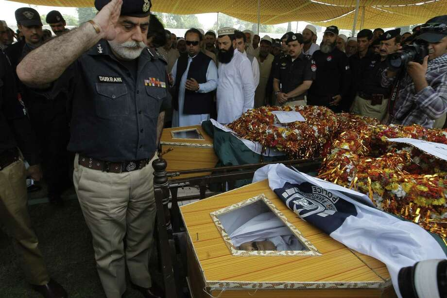 Police chief Nasir Khan Durrani salutes to police officers killed in an attack in Peshawar, Pakistan on Sept. 2, 2015. Three policemen were killed and six others injured when armed gunmen ambushed a raiding police party during a search operation in Urmar Payan area of the provincial capital, official said. Photo: AP Photo/Mohammad Sajjad  / AP