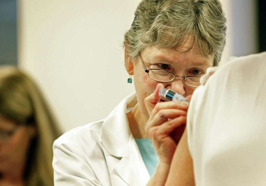 Kathleen Winkworth administers a flu vaccine at Borgess Health and Fitness Center flu clinic in this 2013 file photo. Photo: Ap File Photo  / Kalamazoo Gazette-MLive Media Group