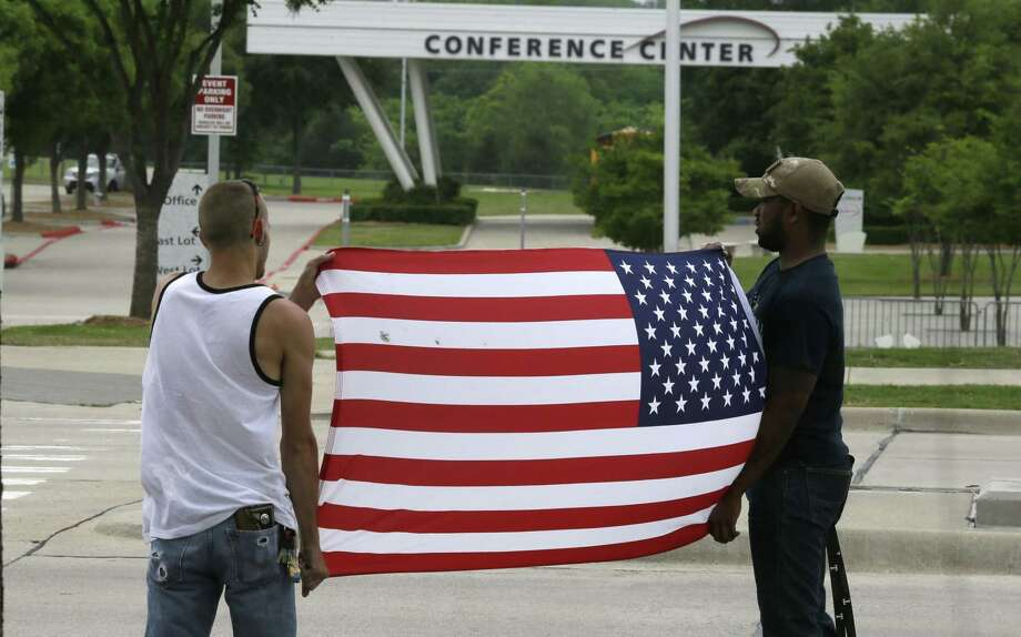Joseph Offutt, right, and Conner McCasland hold a U.S. flag across the street from the Curtis Culwell Center May 5, 2015 in Garland, Texas. A man whose social media presence was being scrutinized by federal authorities was one of two suspects in the Sunday shooting at this location that hosted a cartoon contest featuring images of the Muslim Prophet Muhammad. The Islamic State group on Tuesday claimed responsibility for the attack. Photo: AP Photo/LM Otero  / AP