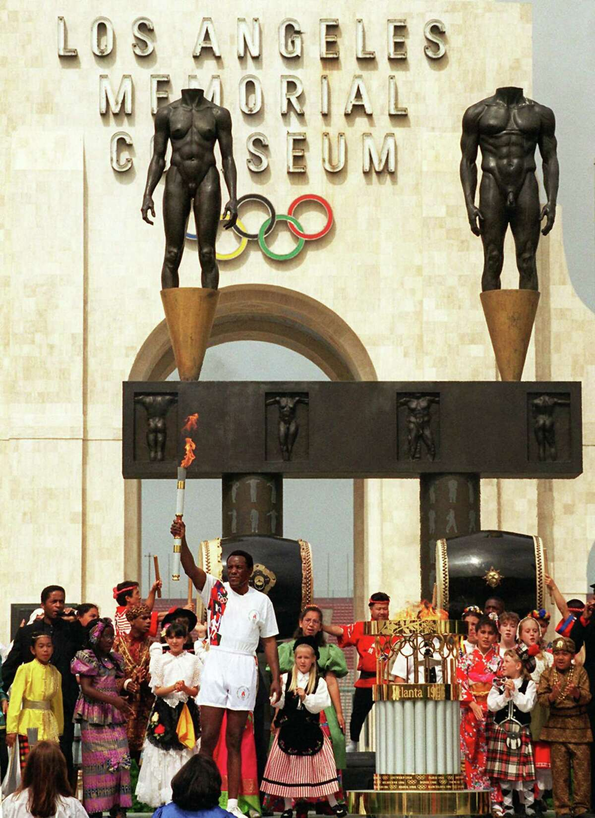 In this April 27, 1996 photo, Olympic decathlon champion Rafer Johnson, who was the last person to carry the torch on its international journey to the 1984 Summer Olympics in Los Angeles, displays the torch with the Olympic flame after its arrival at the Los Angeles Memorial Coliseum in Los Angeles. The U.S. Olympic Committee on Sept. 1, 2015 named Los Angeles as its candidate for the 2024 Games.