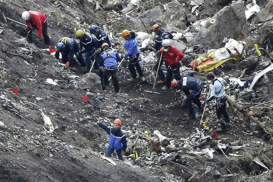 FILE - In this March 26, 2015 file photo, rescue workers work on debris of the Germanwings jet at the crash site near Seyne-les-Alpes, France. The co-pilot of Germanwings Flight 4525 tried a controlled descent on the previous flight that morning to Barcelona before the plane crashed into a mountainside in March on its way back to Germany, French air accident investigators said in a new report released Wednesday May, 6, 2015. Photo: (AP Photo/Laurent Cipriani, File) / AP