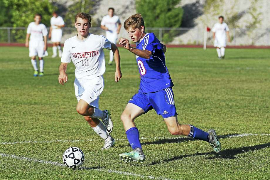 Nonnewaug defender Jacob Matta (blue uniform) came forward for two goals against the Highlanders Tuesday at Northwestern. Photo: Photo By Marianne Killackey  / 2015