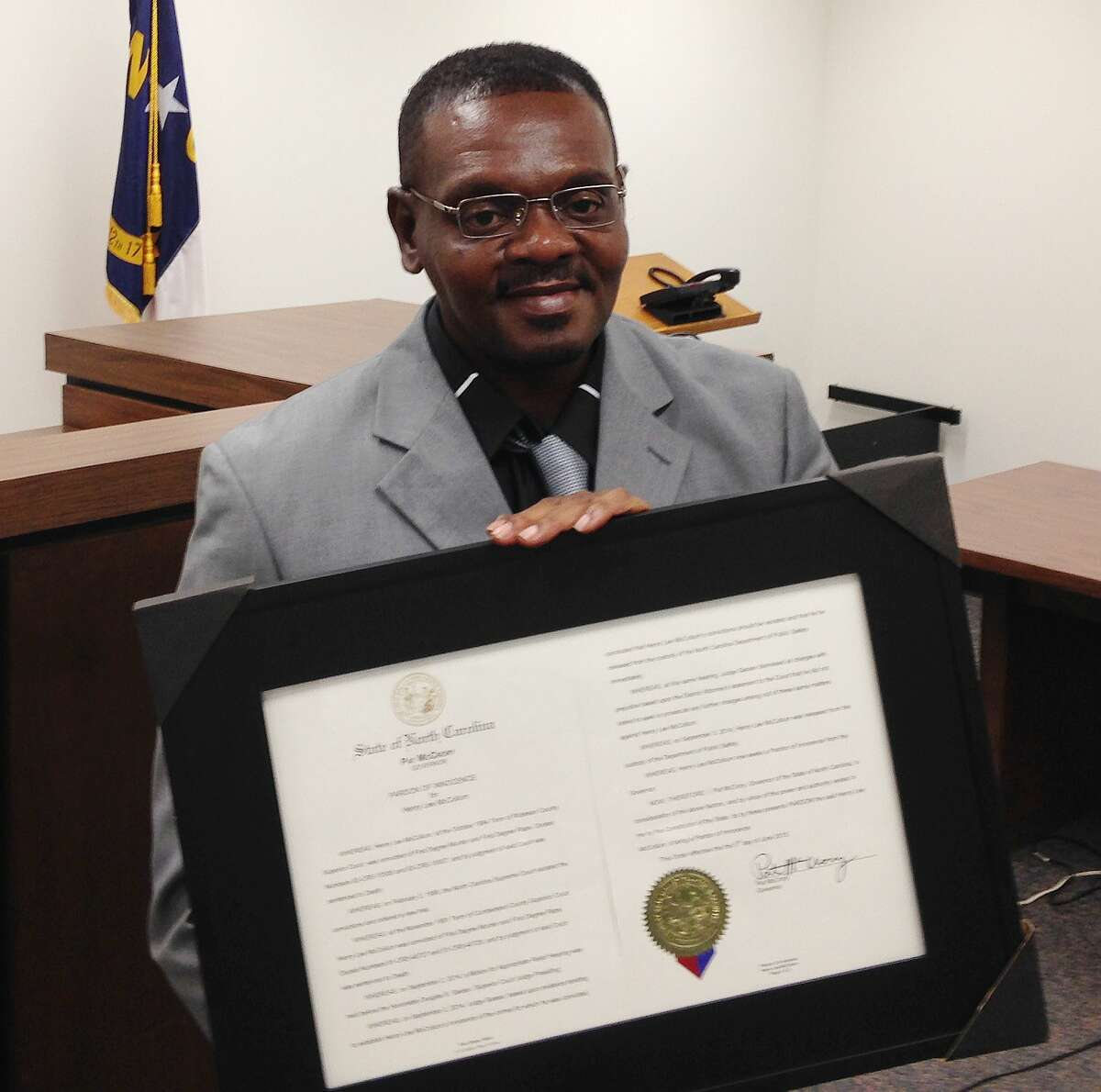 Henry McCollum holds a framed copy of his pardon before a hearing on compensation by the state for his wrongful conviction on Sept. 2, 2015, in Raleigh, N.C. McCollum was the state's longest-serving death row inmate when he was released in 2014 after three decades in prison for being wrongfully convicted in a girl's death.