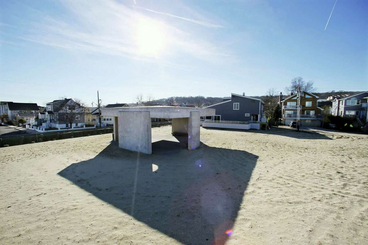 """A large concrete monument stands on the beach behind the Robert D. Wilson Memorial Community Center Wednesday, Jan. 6, 2016, in Highlands, N.J. The state Department of Environmental Protection informed the Highlands borough in November that the more than 1,000-square-foot monument was not permitted under the Coastal Area Facilities Review Act, which oversees development on the state's coastline. The borough is demanding that a trade group remove the monument to survivors of Superstorm Sandy. The monument, dubbed """"Shorehenge,"""" has been criticized by residents for its aesthetics."""