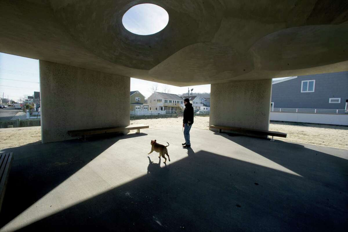 """A man and his dog stand in a large concrete structure on the beach Wednesday, Jan. 6, 2016, in Highlands, N.J. The borough is demanding that a trade group remove the monument to survivors of Superstorm Sandy. A Highlands attorney sent a letter to the Tilt-Up Concrete Association Monday, asking the group to remove the more than 1,000-square-foot monument from the beach. The monument is dubbed """"Shorehenge."""""""