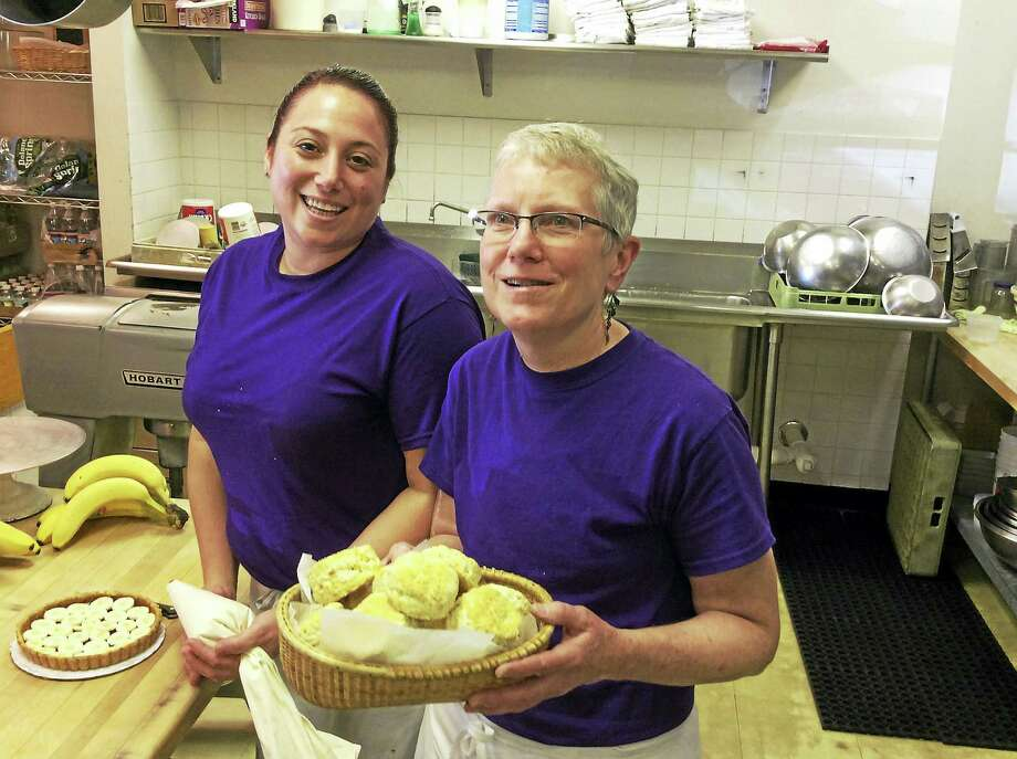 Nancy Ackermann, owner of Guilford's 4 & Twenty Blackbirds Bakeshop in Guilford, holds a basket of freshly prepared leek and black pepper biscuits with Annie Cobb, left. Photo: Stephen Fries — Special To The Register