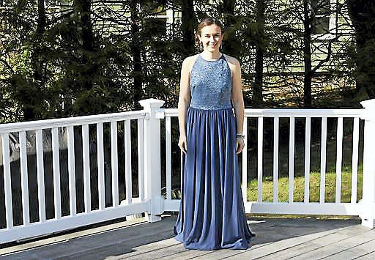 In this April 15, 2016 photo provided by Jennifer Goodwin, Jillian Dalton wears Catherine Malatesta's prom dress at her home in Arlington, Mass., before attending the Arlington High School prom. After Catherine died from a rare cancer on Aug. 2, 2015, her friends decided each of them would wear Catherine's gown to their own proms to honor her and remember the happiness she exuded on that special night.