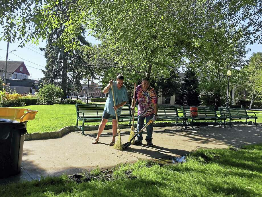 Volunteers and members of the Torrington Police Department lent a hand cleaning up Coe Memorial Park Friday, as the first step in an effort to beautify the downtown. Photo: Ben Lambert — The Register Citizen