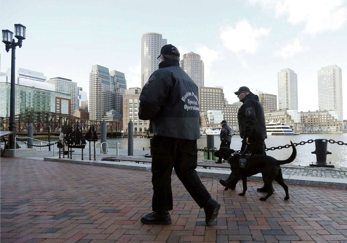 Boston police officers and a K-9 dog patrol outside the federal courthouse in Boston, Monday, Jan. 5, 2015, on the first day of jury selection in the trial of Boston Marathon bombing suspect Dzhokhar Tsarnaev. (AP Photo/Elise Amendola)