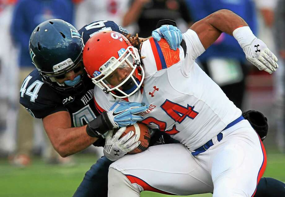 Villanova linebacker Don Cherry (44) of Trumbull tackles Sam Houston State running back Donavan Williams during an FCS quarterfinal game last December in Villanova, Pa. Photo: Laurence Kesterson — The Associated Press File Photo  / FR170723 AP