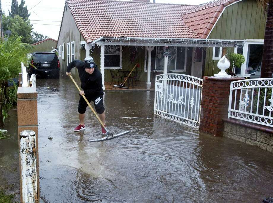 A resident of one of the houses on E. McFadden Avenue in Santa Ana, Calif., squeegees water out of the driveway of the home, Wednesday, Jan. 6, 2016.  El Nino storms lined up in the Pacific, promising to drench parts of the West for more than two weeks and increasing fears of mudslides and flash floods in regions stripped bare by wildfires. At least two more storms are expected to follow bringing as much as 3 inches of rain. Photo: Sam Gangwer/The Orange County Register Via AP / The Orange County Register