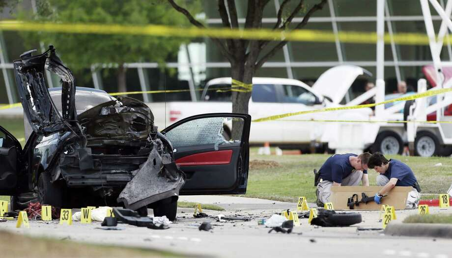 Investigators box up an assault weapon outside the Curtis Culwell Center on Monday, May 4, 2015 in Garland, Texas. Two men opened fire with assault weapons on police Sunday night who were guarding a provocative contest for Prophet Muhammed cartoons. Photo: AP Photo/Brandon Wade  / FR168019 AP
