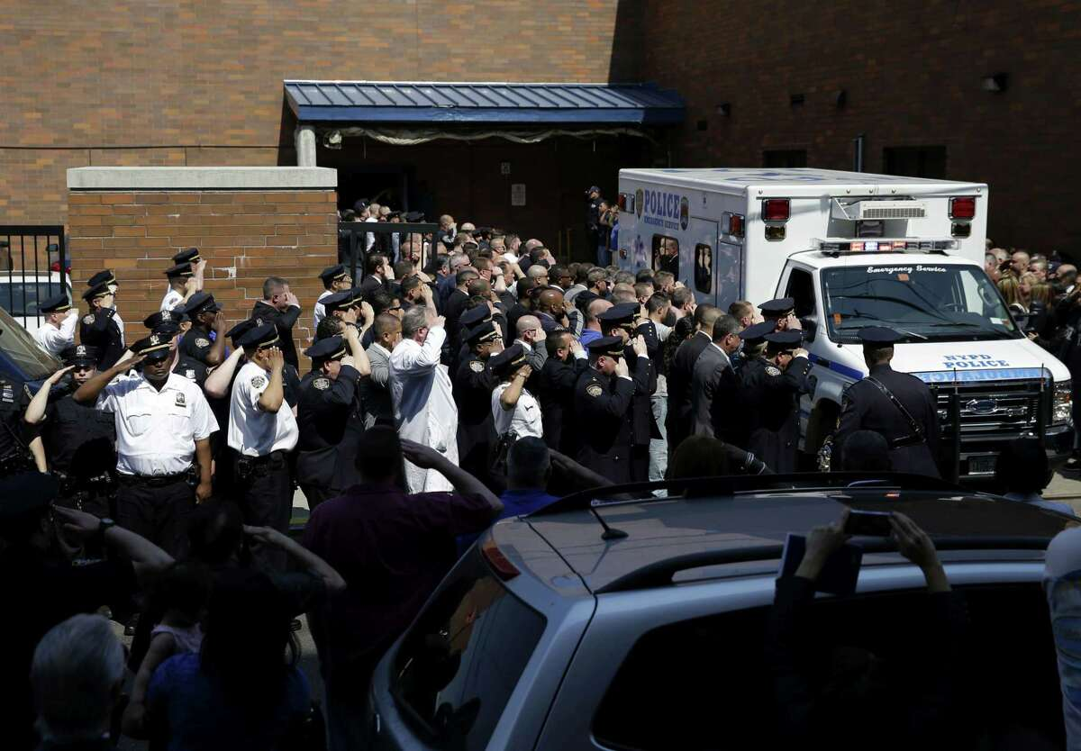 Police officers salute as the body of Brian Moore leaves Jamaica Hospital in New York, Monday, May 4, 2015. A 25-year-old police officer shot in the head over the weekend while attempting to stop a man suspected of carrying a handgun has died from his injuries, the third New York Police Department officer slain in the line-of-duty in five months, a City Hall official said Monday.