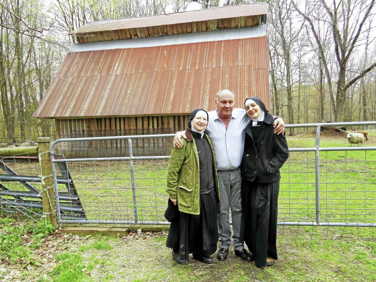 Frank Martinelli poses with Sister Jadwiga and Sister Alma in front of the barn needing roof repairs at the Abbey of Regina Laudis.