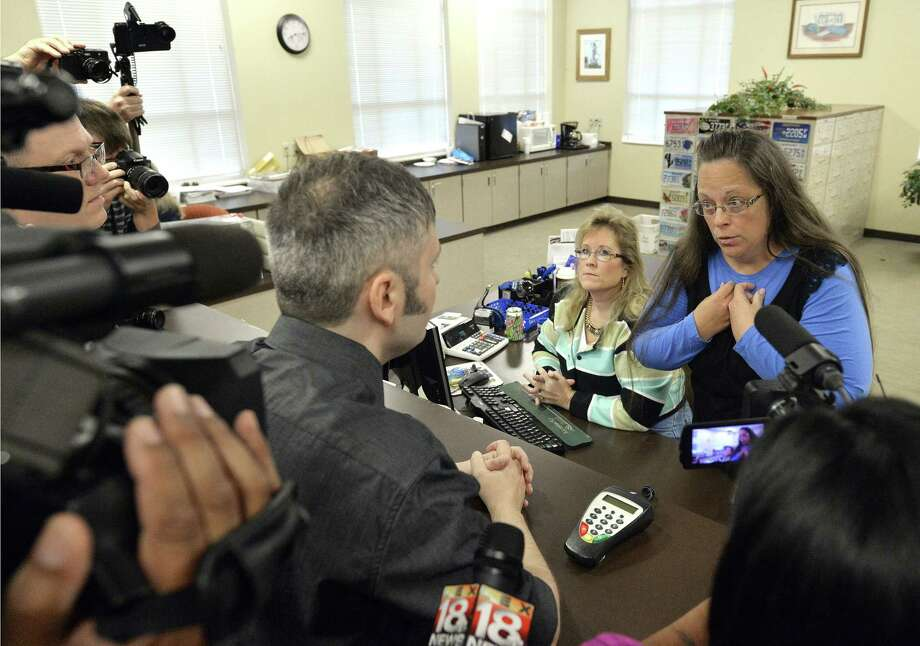 Rowan County Clerk Kim Davis, right, talks with David Moore following her office's refusal to issue marriage licenses at the Rowan County Courthouse in Morehead, Ky. on Sep. 1, 2015. Although her appeal to the U.S. Supreme Court was denied, Davis still refuses to issue marriage licenses. Photo: AP Photo/Timothy D. Easley  / FR43398 AP