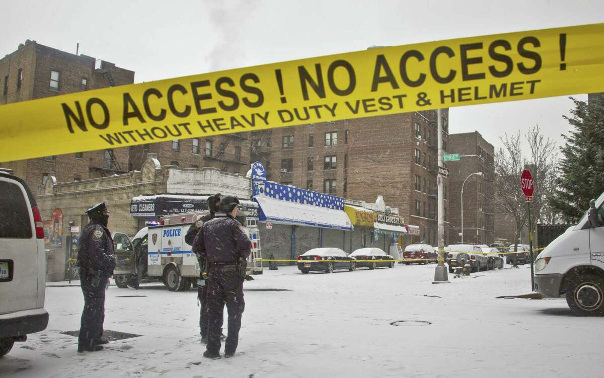 Police secure area with yellow tape where police and suspects exchanged gunfire, Tuesday, Jan. 6, 2015, in New York. A manhunt was under way Tuesday for at least two suspects who shot and wounded two New York City plainclothes police officers responding to a robbery Monday in the Bronx.