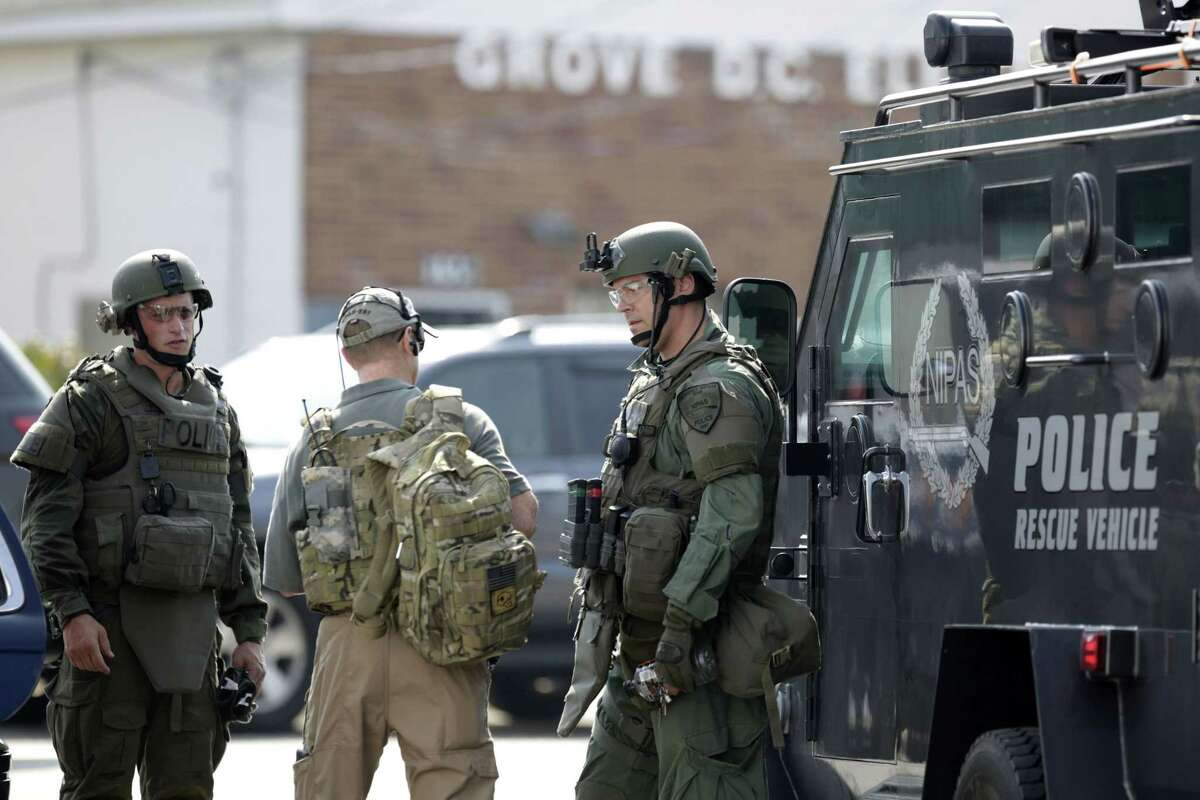 Police officers gather before heading out for a manhunt after an officer was shot in Fox Lake, Ill., on Tuesday, Sept. 1, 2015. Lake County Major Crimes Task Force Cmdr. George Filenko says an officer was shot Tuesday morning in Fox Lake, 55 miles north of Chicago.