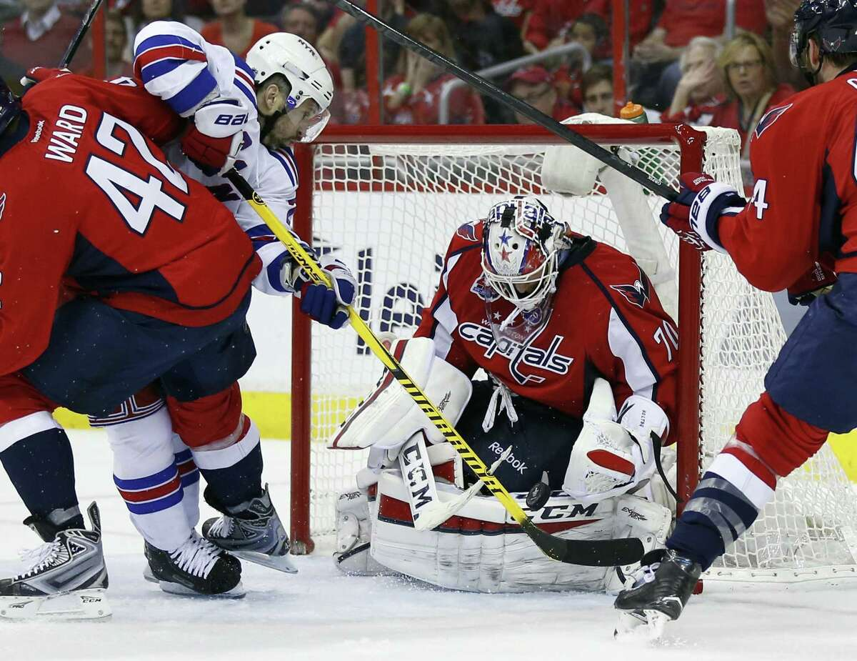 Rangers right wing Martin St. Louis (26) reaches over Capitals right wing Joel Ward (42) as goalie Braden Holtby blocks the shot during the second period on Monday.