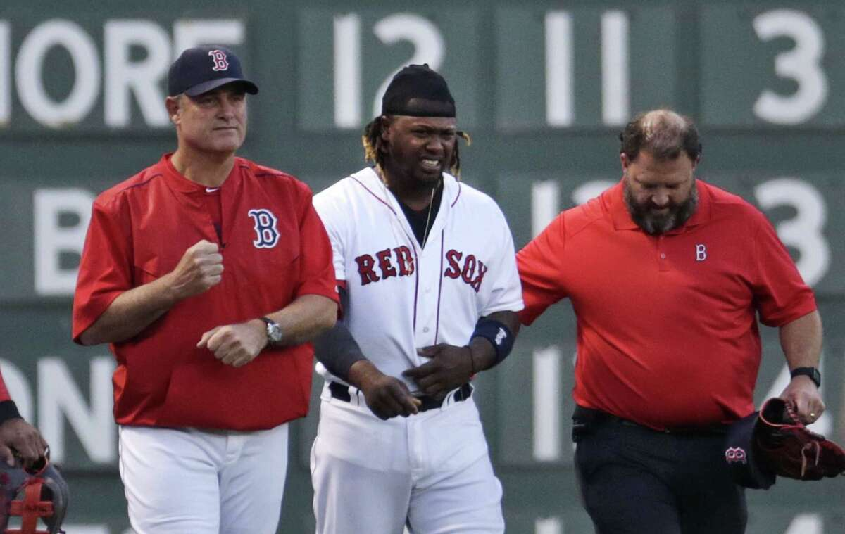 Red Sox left fielder Hanley Ramirez is helped from the field by manager John Farrell, left, and trainer Rick Jameyson during the first inning on Monday.