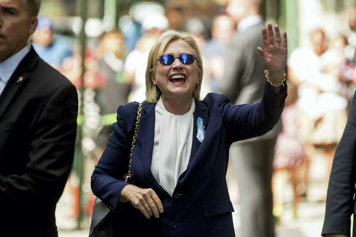 """Democratic presidential candidate Hillary Clinton waves after leaving an apartment building on Sept. 11, 2016, in New York. Clinton's campaign said the Democratic presidential nominee left the 9/11 anniversary ceremony in New York early after feeling """"overheated."""""""