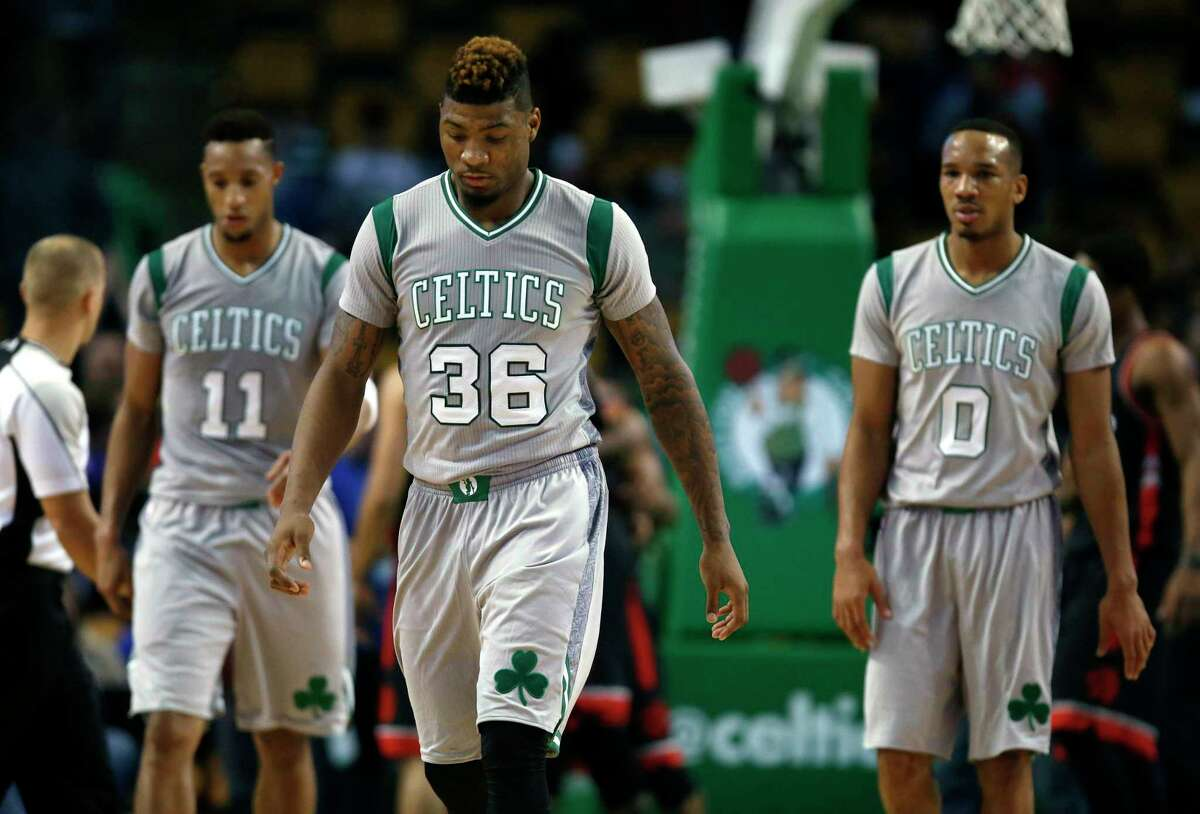 The Celtics' Marcus Smart (36), Evan Turner (11) and Avery Bradley (0) leave the court after losing 113-103 to the Toronto Raptors in Boston.