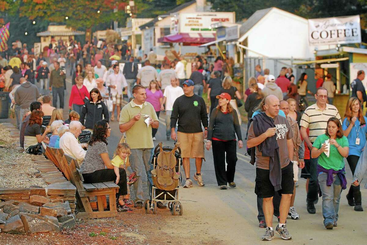 Fairgoers walk down one of several midways at the Durham Fair in 2012.
