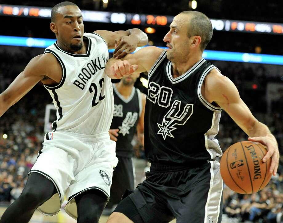 Brooklyn Nets guard Markel Brown defends Spurs guard Manu Ginobili on Friday in San Antonio. Photo: Bahram Mark Sobhani — The Associated Press  / FR91484 AP