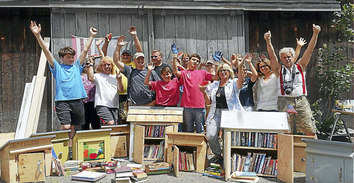 Library builders celebrate their accomplishments. Pictured are Little Free Library Steward Rose Buckens, third from right, and Harvey Hubbell, far right, and all the volunteers at the box-building workshop at Hubbell's farm on July 2.