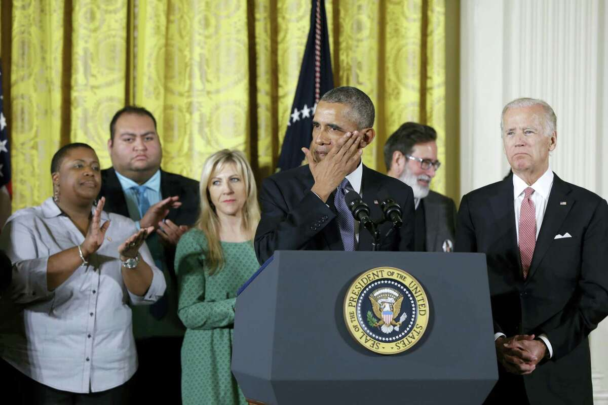 President Barack Obama, joined by Vice President Joe Biden and gun violence victims, wipes a tear from his cheek as speaks in the East Room of the White House in Washington, Tuesday, Jan. 5, 2016, about steps his administration is taking to reduce gun violence. Also on stage are stakeholders, and individuals whose lives have been impacted by the gun violence.