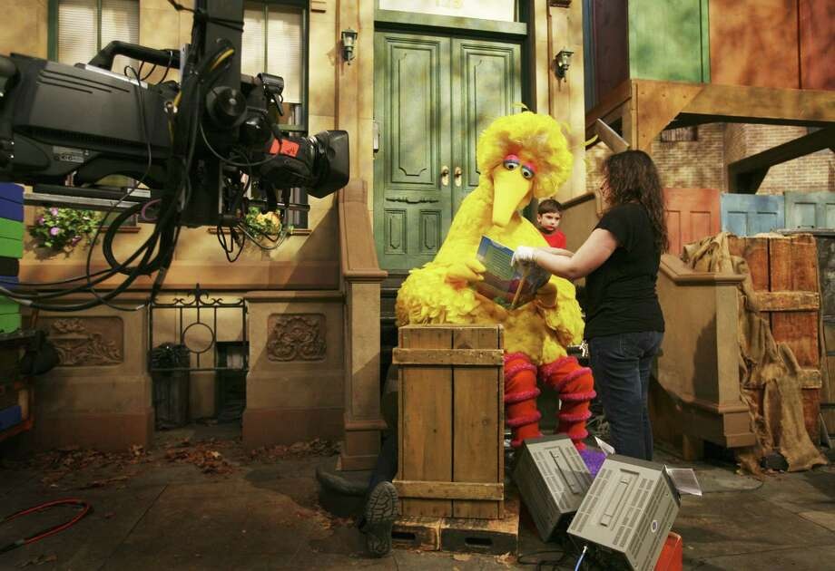 In this 2008 file photo, Michelle Hickey, a Muppet wrangler adjusts a book for Big Bird, voiced by Carroll Spinney, so he can read to Connor Scott during a taping of Sesame Street in New York. Photo: Associated Press  / AP