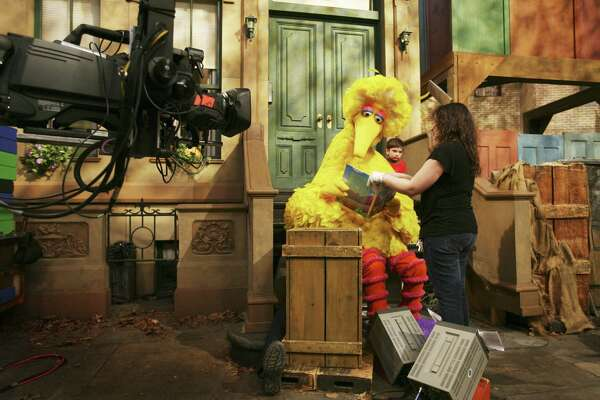 In this 2008 file photo, Michelle Hickey, a Muppet wrangler adjusts a book for Big Bird, voiced by Carroll Spinney, so he can read to Connor Scott during a taping of Sesame Street in New York.