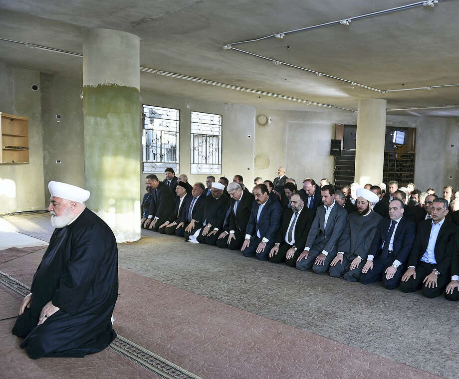 In this photo released on the official Facebook page of the Syrian Presidency, Syrian President Bashar Assad, fourth right, prays at the dawn Eid al-Adha prayers at the Saad ibn Muaaz Mosque in Daraya, a blockaded Damascus suburb, Syria on Sept. 12, 2016. Photo: Syrian Presidency Via Facebook  / Facebook page of the Syrian Presidency
