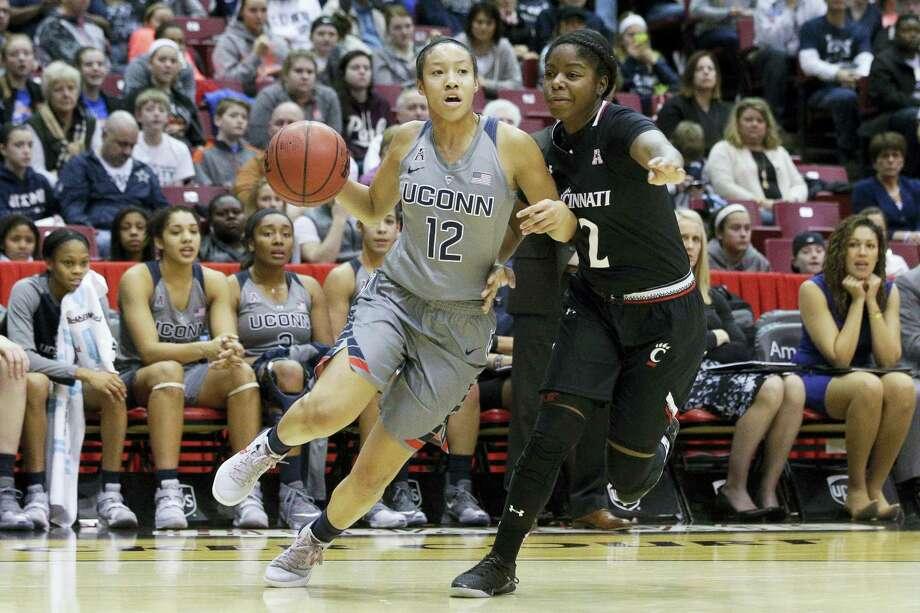 Connecticut's Saniya Chong (12) drives around Cincinnati's Nikira Goings (2) in the second half of an NCAA college basketball game, Wednesday, Dec. 30, 2015, in Cincinnati. Connecticut won 107-45. (AP Photo/John Minchillo) Photo: AP / AP