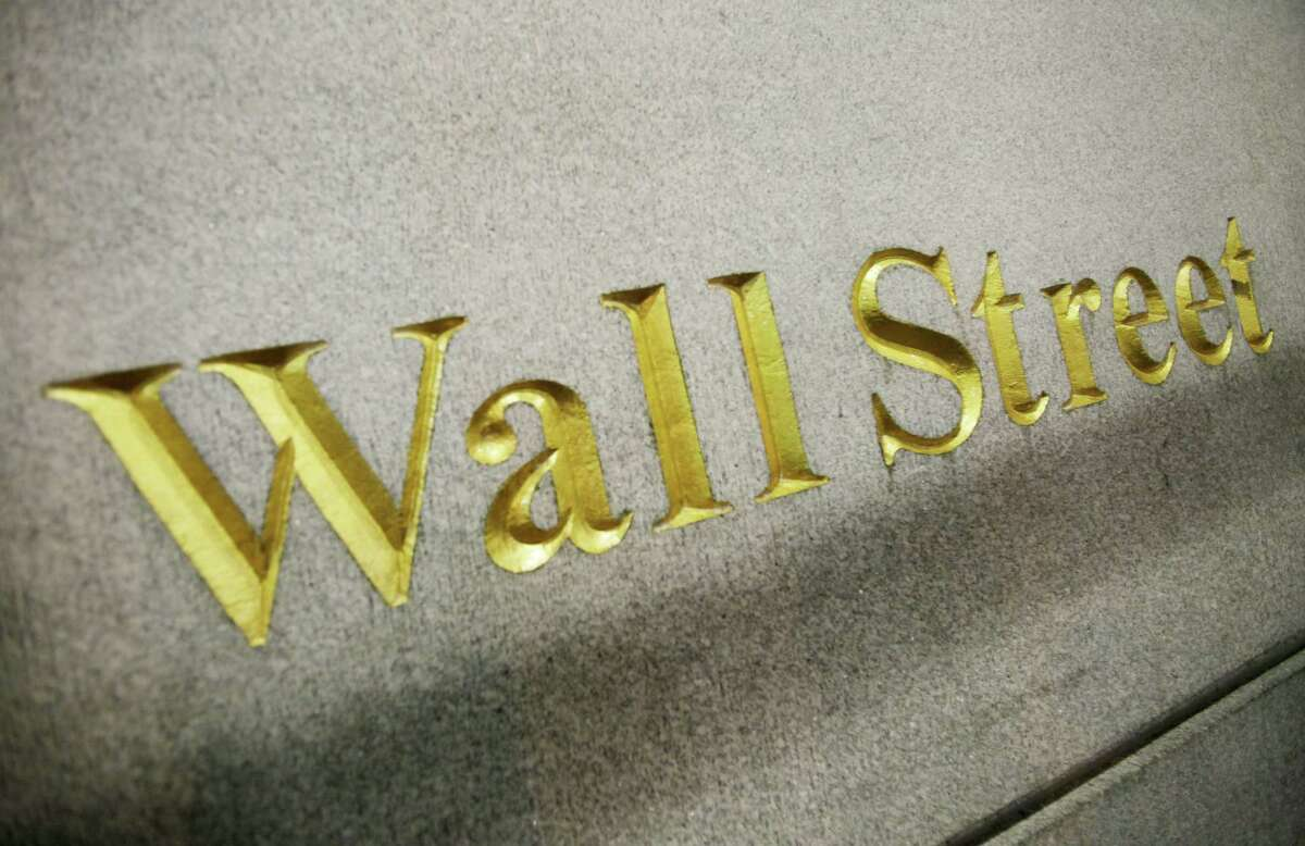 FILE - This Oct. 8. 2014 photo shows a Wall Street address on the side of a building in New York. U.S. stocks opened higher Monday, May 4, 2015, pushing stocks to record levels, as investors assessed corporate earnings.