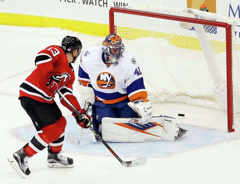 New Jersey Devils left wing Mike Cammalleri, left, scores the winning goal on the New York Islanders' Jaroslav Halak during a shootout Saturday in Newark, N.J. Photo: Julio Cortez — The Associated Press  / AP