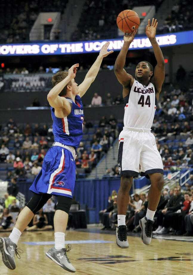 UConn's Rodney Purvis, right, shoots over UMass-Lowell's DJ Mlachnik, left, earlier this season. Photo: The Associated Press File Photo  / FR125654 AP