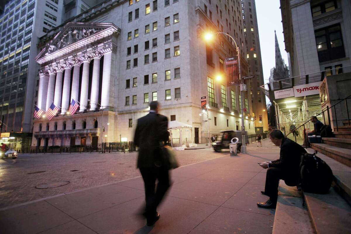In this file photo, a man walks to work on Wall Street, near the New York Stock Exchange, in New York.