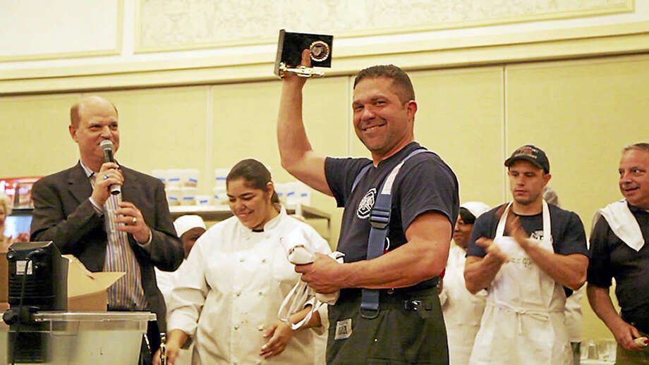 New Haven firefighter Billy DiLegge celebrates with the trophy after winning the ninth annual Iron Chef Elm City competition on May 1. Photo: Photo Courtesy Of Megan Lang