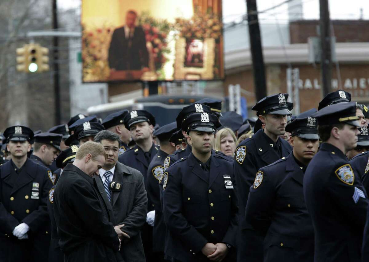 Some police officers turn their back to a large screen that displays New York City Mayor Bill de Blasio speaking during the funeral of Officer Wenjian Liu.
