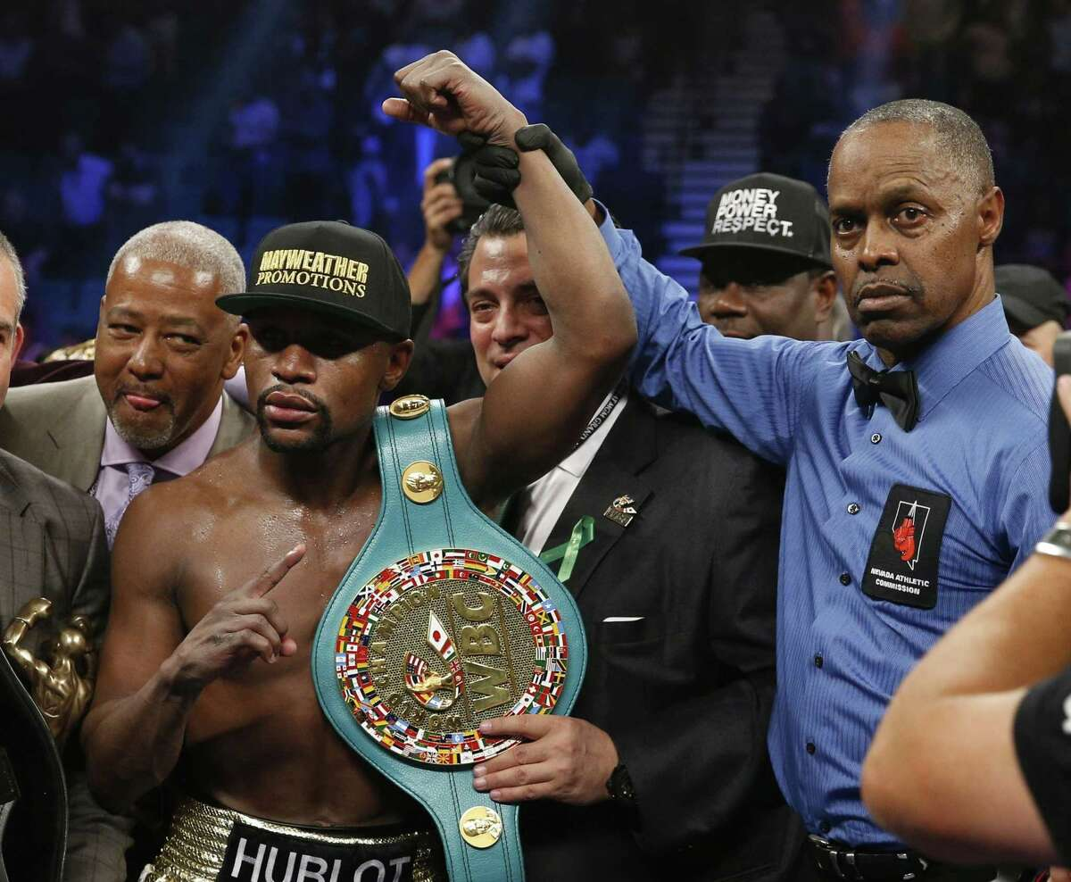 Floyd Mayweather Jr., left, holds up the title belt next to referee Kenny Bayless after his win against Manny Pacquiao on Saturday in Las Vegas.
