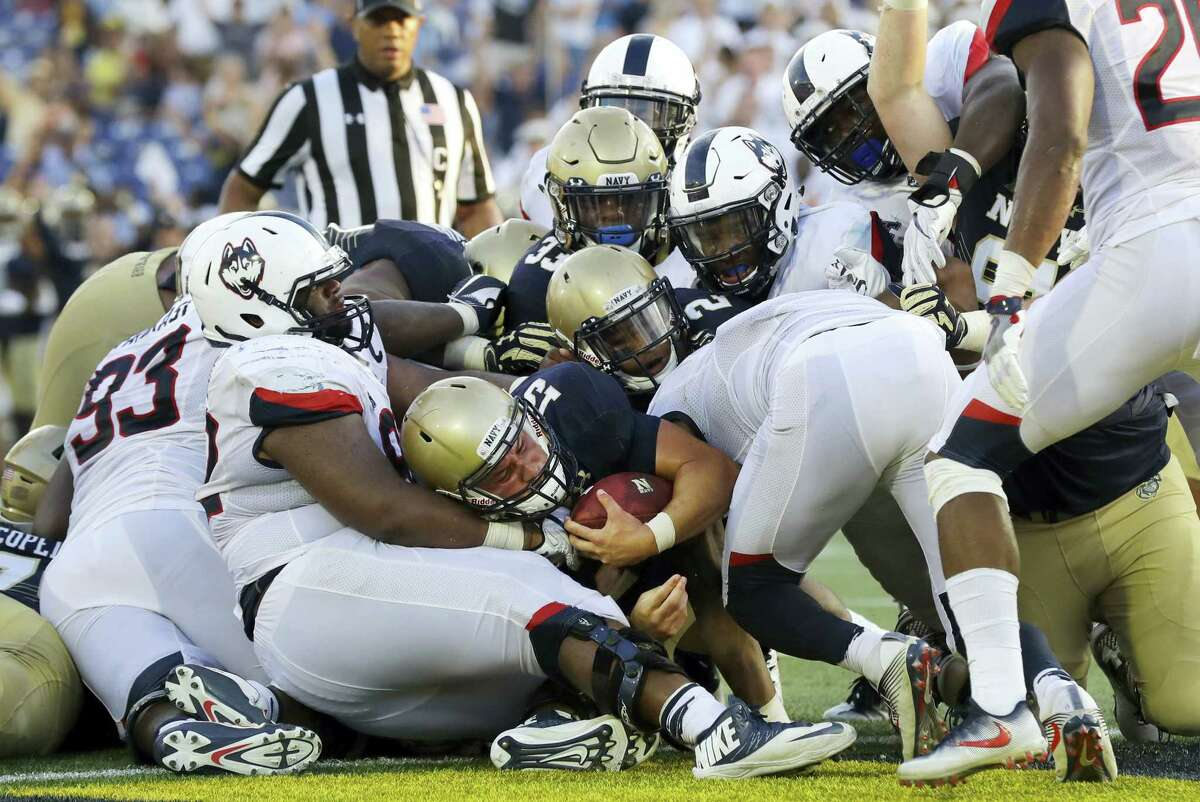 Navy quarterback Will Worth, center, falls into the end zone for a touchdown in the second half of an NCAA college football game against Connecticut in Annapolis, Md. on Sept. 10, 2016. Navy won 28-24.