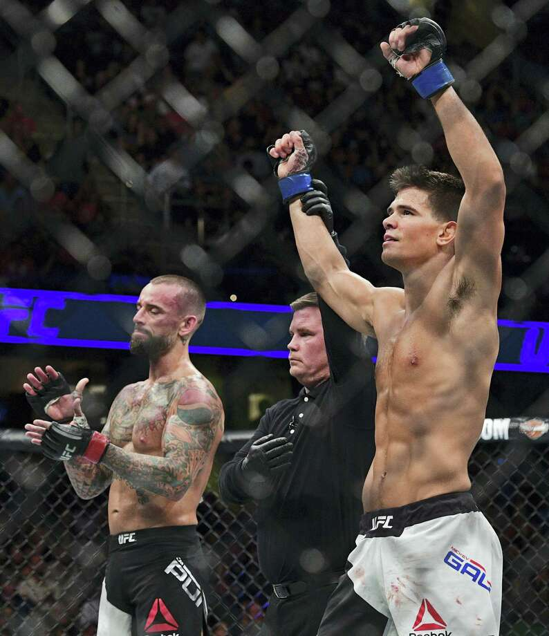 Mickey Gall has his arm raised by the referee after defeating CM Punk during a welterweight bout at UFC 203 on Saturday in Cleveland. Photo: David Dermer — The Associated Press  / FR171035 AP