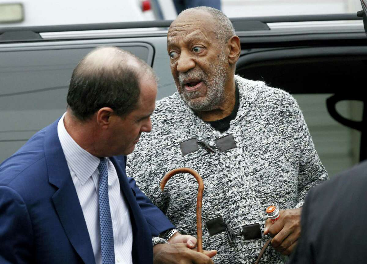 Comedian Bill Cosby is helped as he arrives for a court appearance in Elkins Park, Pa., Wednesday. Cosby was arrested and charged with drugging and sexually assaulting a woman at his home in January 2004.