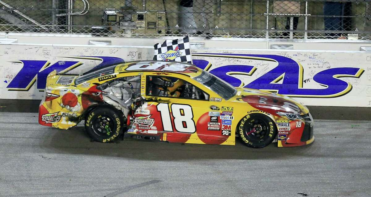 Kyle Busch celebrates with the checkered flag after winning at Kansas Speedway on Saturday night.