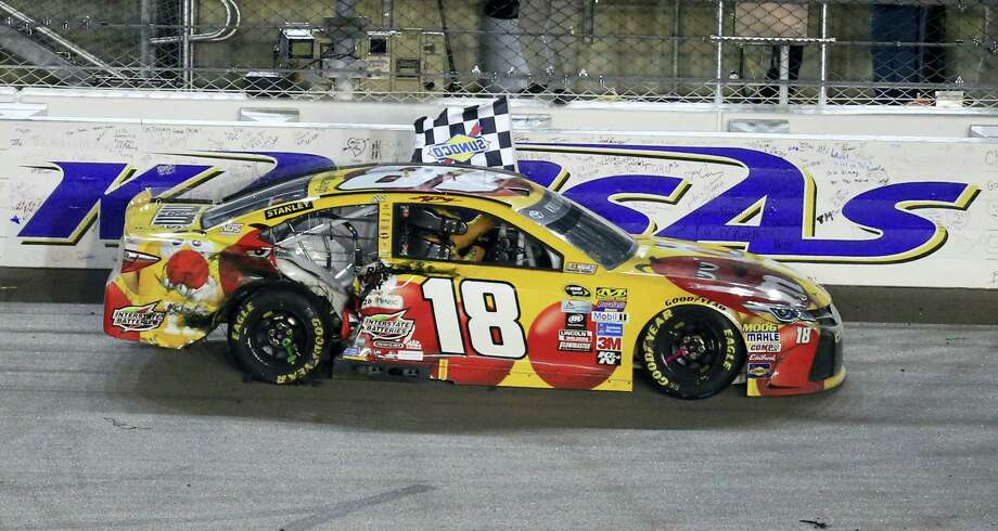 Kyle Busch celebrates with the checkered flag after winning at Kansas Speedway on Saturday night. Photo: Orlin Wagner — The Associated Press  / Copyright 2016 The Associated Press. All rights reserved. This material may not be published, broadcast, rewritten or redistribu