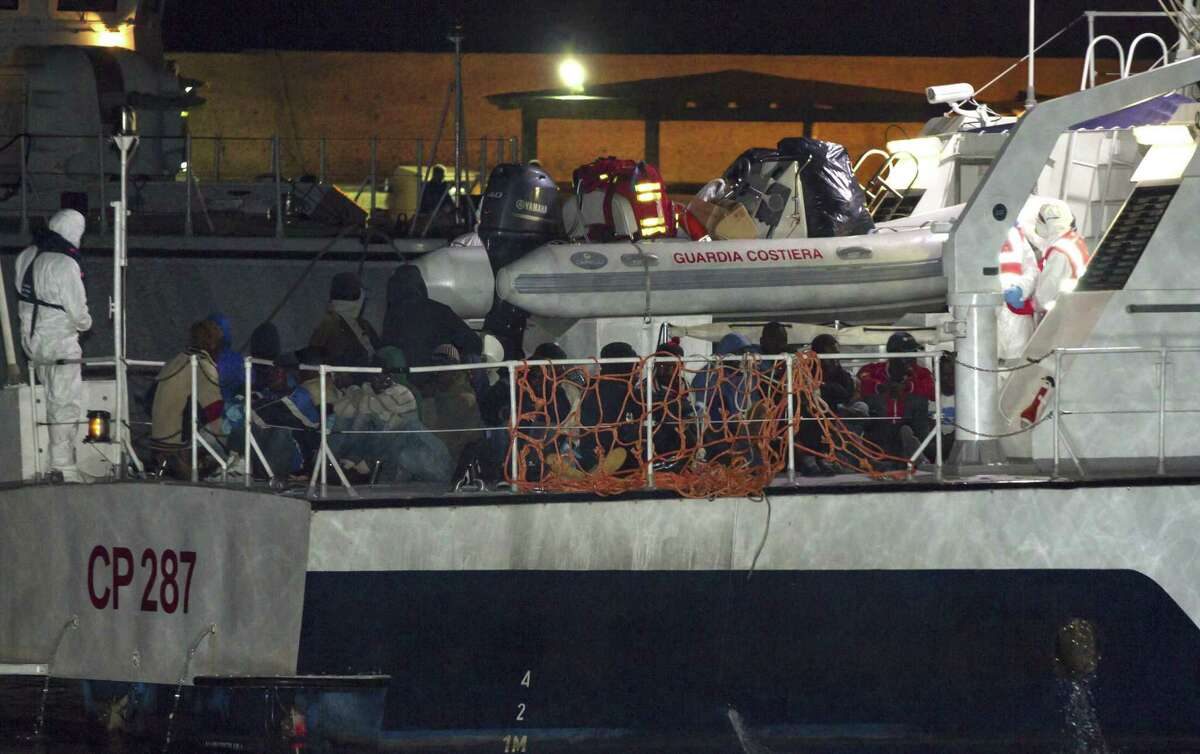 Migrants arrive at the Lampedusa island harbor aboard an Italian Coast Guard ship early Sunday, May 3, 2015. Ships rescued 3,690 migrants in just one day from smugglers' boats on the Mediterranean Sea off the Libyan coast, the Italian Coast Guard said.
