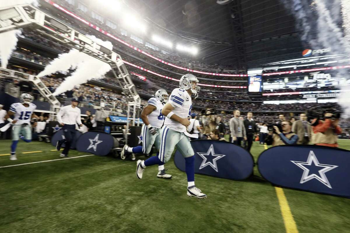 Dallas quarterback Tony Romo leads the Cowboys onto the field before a Dec. 21 game against the Indianapolis Colts in Arlington, Texas.