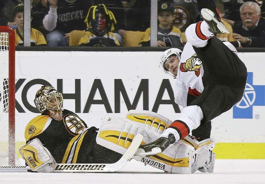 The Ottawa Senators' Bobby Ryan, right, trips over Boston Bruins goalie Tuukka Rask after scoring the winning goal in overtime on Saturday in Boston. Photo: Michael Dwyer — The Associated Press  / AP