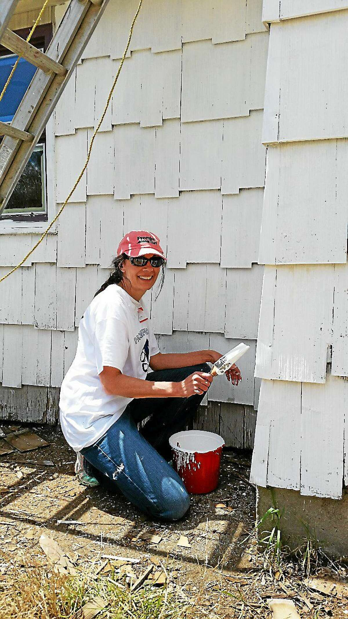 Photo by N.F. Ambery Volunteer Linda McCormick of Litchfield paints the exterior of Stephen Rosko Jr.'s house on Saturday.