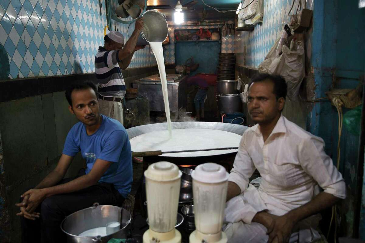 An Indian restaurant worker pours milk into a large vessel in New Delhi, India.